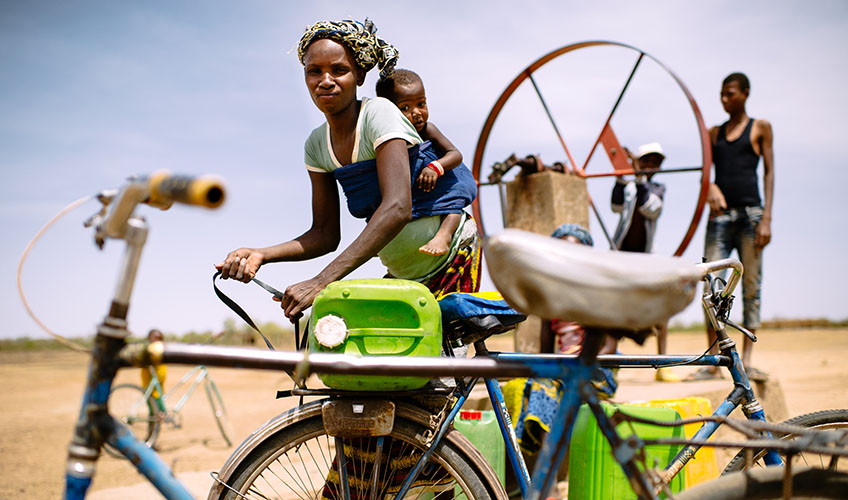 Woman with baby on her back untying a jerry can from a bicycle as she prepares to collect water. Two other people stand behind her at a pump.