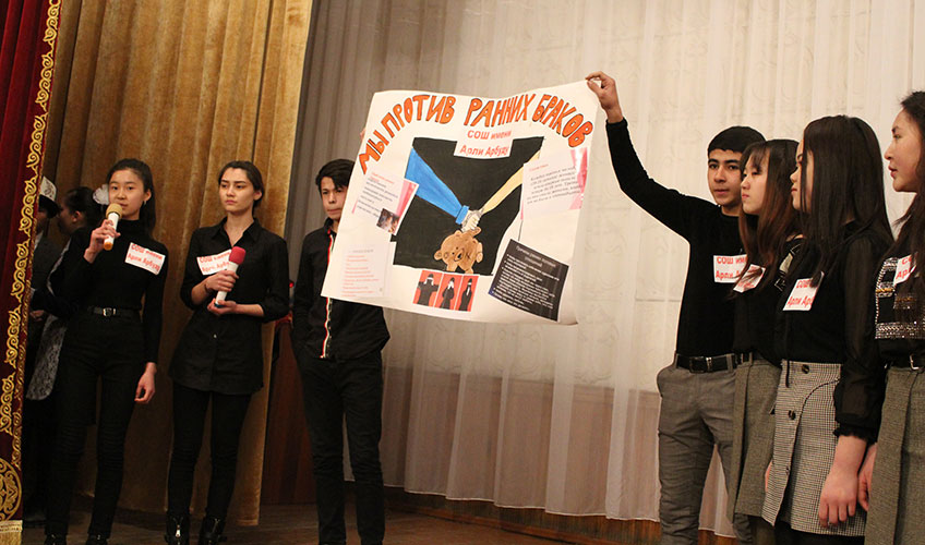 Students holding up a poster which says 'we are against early marriages'