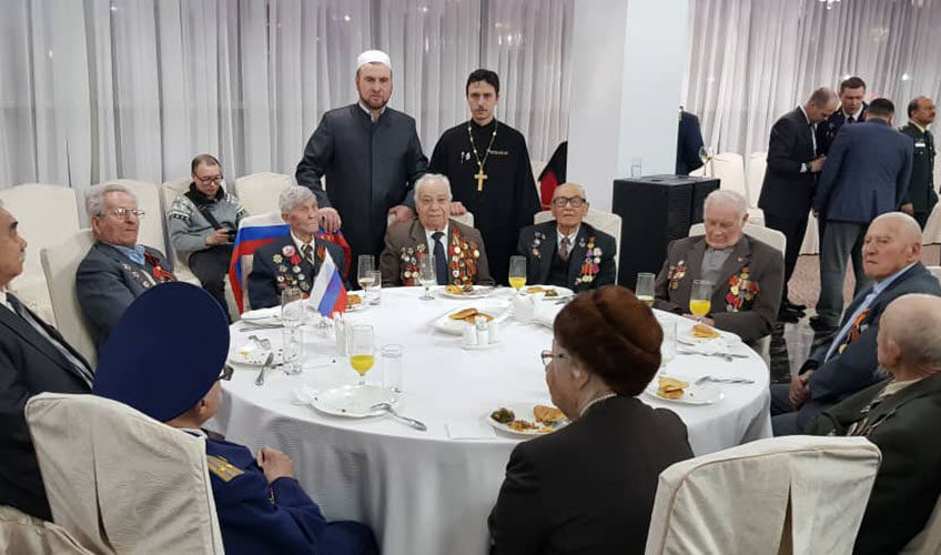 Imam Muhammad Durgalov interacts with a group of men.