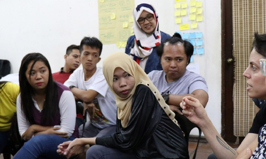 Naila and other PV participants listen intently to the facilitator