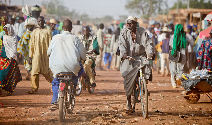 People walk and ride bicycles through a market in Burkina Faso