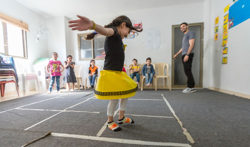 A girl in a bright yellow skirt jumps through squares marked on the floor as other children and an adult look on.
