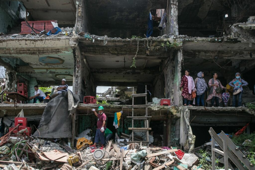 A rescue worker walks through the ruins of a building